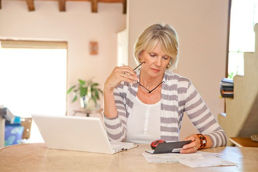 Woman working at home office with computer and bills : Stock Photo