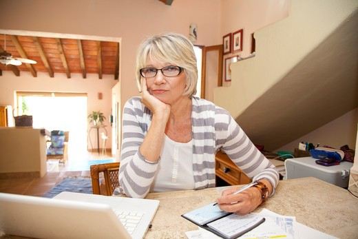 Woman writing checks in home office : Stock Photo