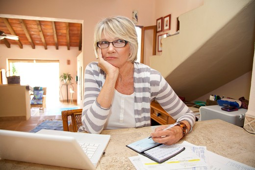 Stock Photo: 1530R-42063 Woman writing checks in home office