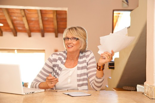 Stock Photo: 1530R-42064 Woman in home office holding bills