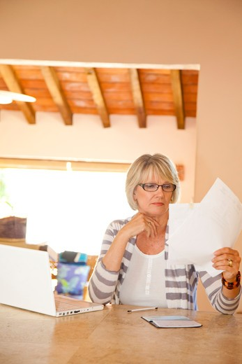 Woman in home office holding bills : Stock Photo