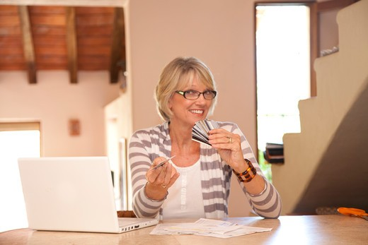 Stock Photo: 1530R-42068 Woman at home office with credit cards