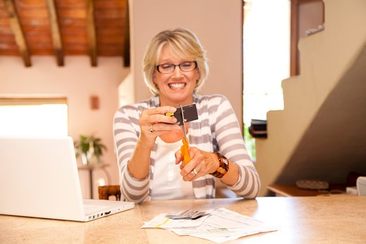 Woman at home office cutting up credit cards : Stock Photo