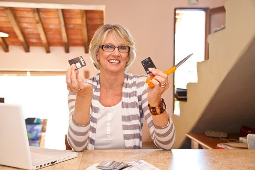 Stock Photo: 1530R-42072 Woman at home office cutting up credit cards