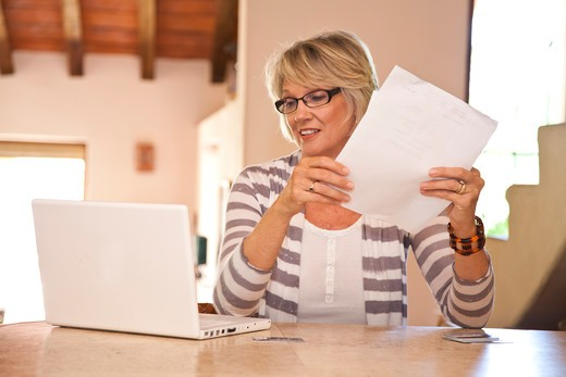 Stock Photo: 1530R-42073 Woman at home office holding bills and looking at laptop,