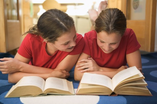 Twin teenage girls doing their homework together.   : Stock Photo