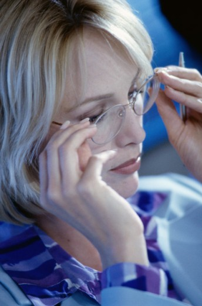 Businesswoman adjusting her eyeglasses : Stock Photo