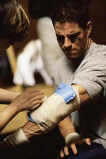 Close-up of a person dressing a man's injured hand : Stock Photo