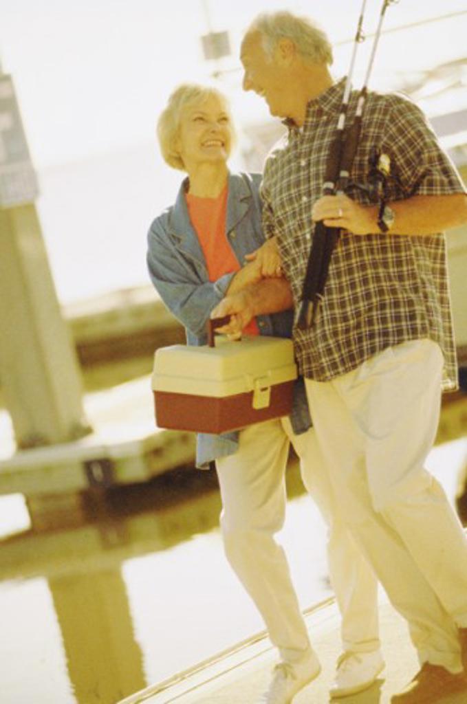 Senior couple walking together holding fishing equipment : Stock Photo