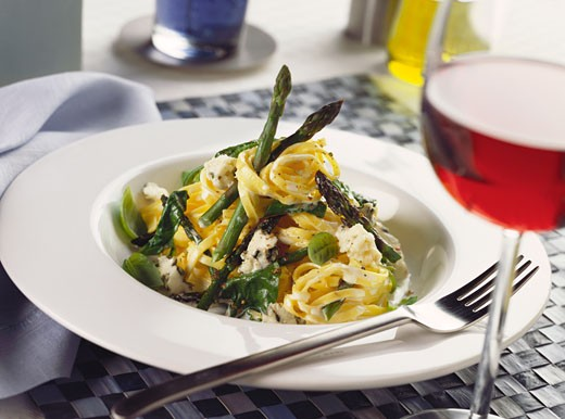 Ribbon pasta on green asparagus & gorgonzola; glass of red wine : Stock Photo
