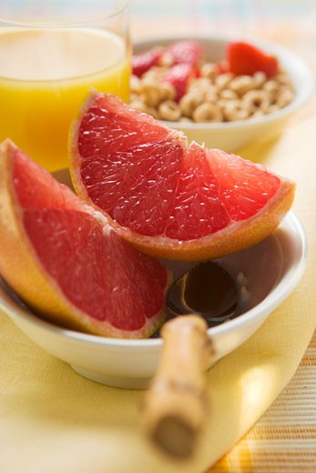 Grapefruit wedges in a bowl, cereal behind : Stock Photo