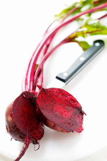 Beetroot with leaves, halved; knife : Stock Photo