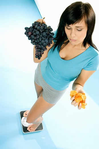 Stock Photo: 1532R-12305 Young woman standing on scales with crisps and grapes