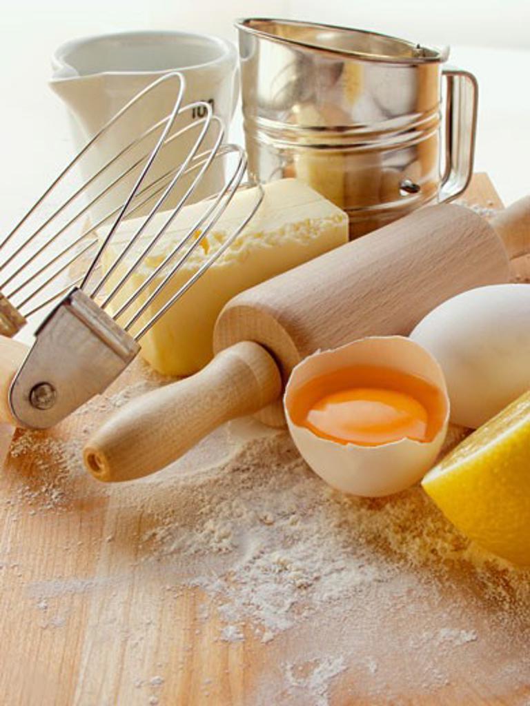 Various baking utensils, eggs, butter and lemon : Stock Photo