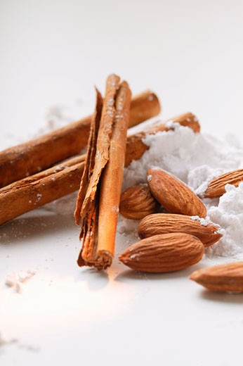 Cinnamon sticks, almonds and icing sugar : Stock Photo
