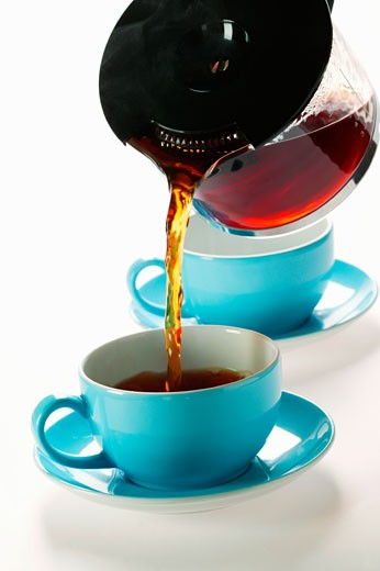 Pouring coffee out of glass coffee pot into blue cup : Stock Photo
