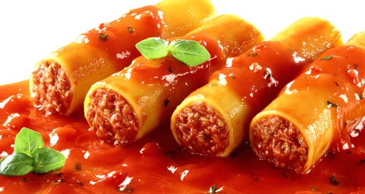 Cannelloni with mince filling and tomato sauce : Stock Photo
