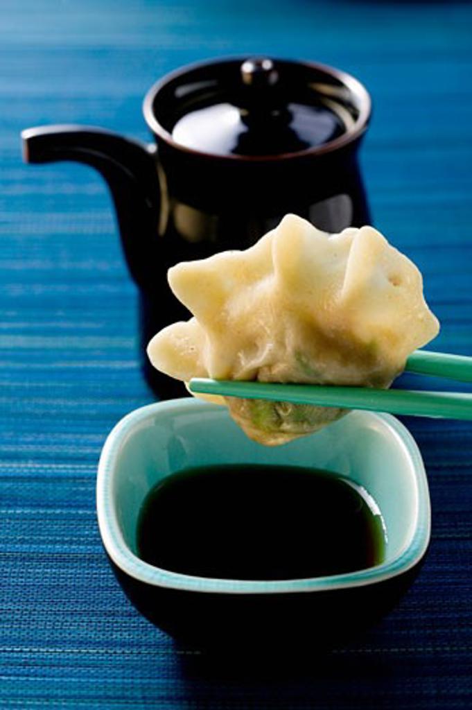 Pasta parcel on chopsticks above soy sauce : Stock Photo