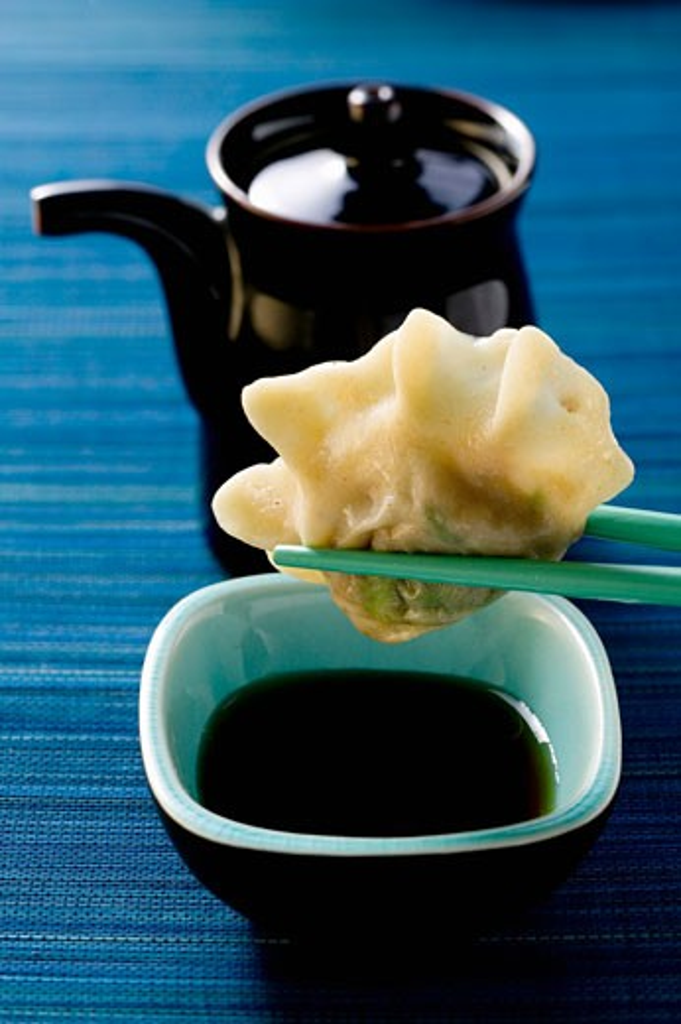 Stock Photo: 1532R-16948 Pasta parcel on chopsticks above soy sauce