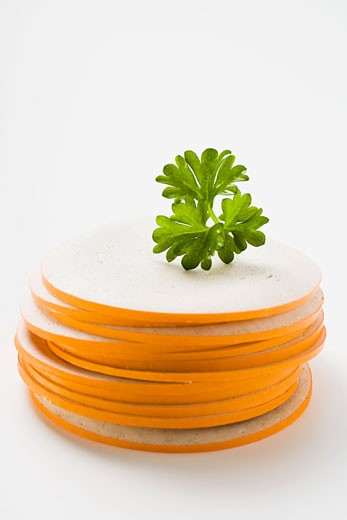 Slices of Gelbwurst (pork & veal sausage) in a pile with parsley : Stock Photo