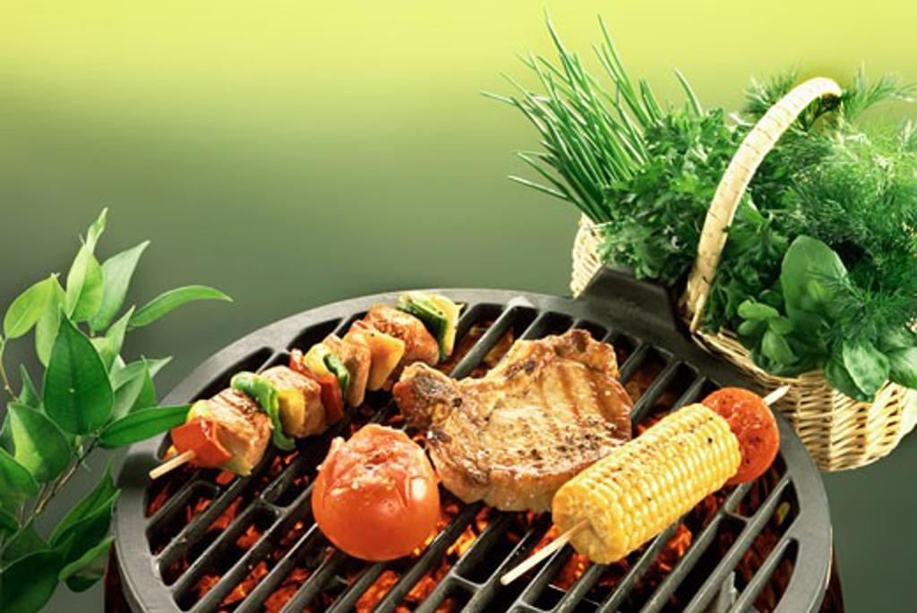 Chop, kebab, sweetcorn and tomato on barbecue; fresh herbs : Stock Photo