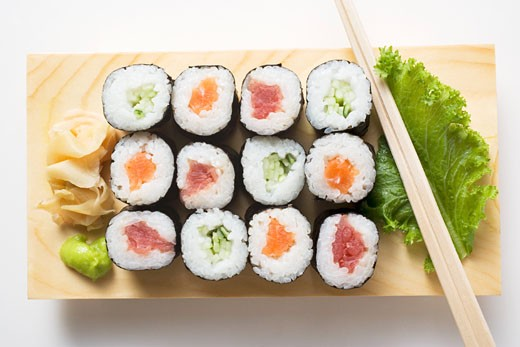 Stock Photo: 1532R-18476 Maki sushi with fish and cucumber on sushi board