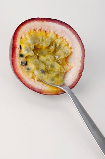Half of a passion fruit being hollowed out : Stock Photo