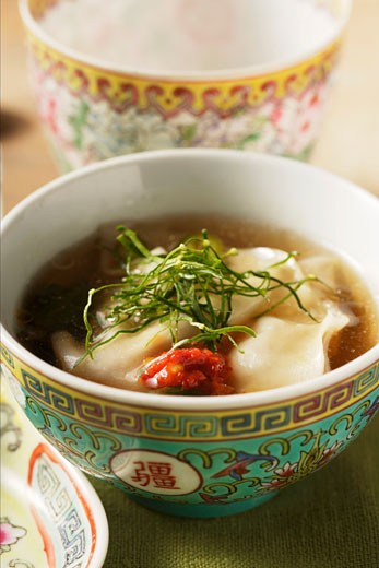 Broth with won tons, chili sauce & strips of lemon leaves : Stock Photo