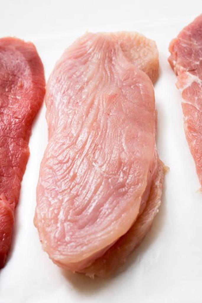 Turkey escalope between veal and pork escalopes : Stock Photo