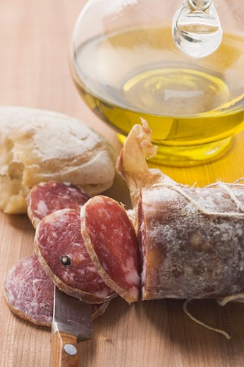Italian salami, partly sliced, white bread, olive oil : Stock Photo