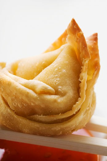 Stock Photo: 1532R-20678 One deep-fried wonton with sweet and sour sauce (close-up)