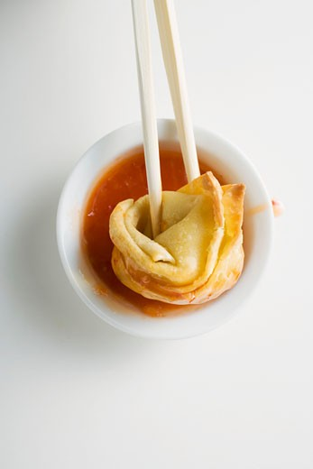 Stock Photo: 1532R-20681 Dipping a deep-fried wonton in sweet and sour sauce
