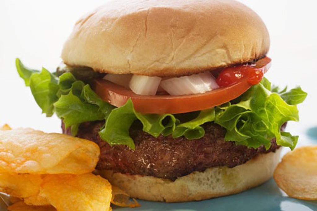 Hamburger with tomato, onions, ketchup and crisps : Stock Photo