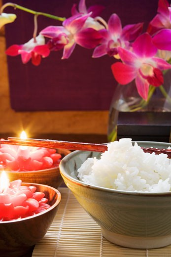 Bowl of rice beside burning candles (Thailand) : Stock Photo