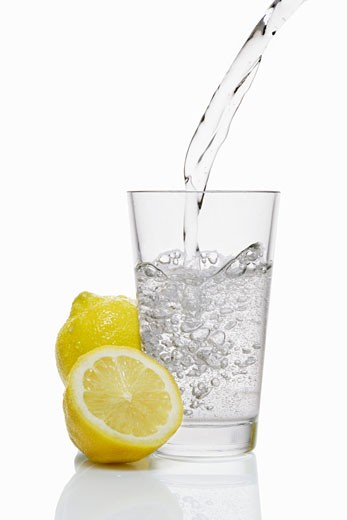 Stock Photo: 1532R-22129 Pouring water into a glass & lemons