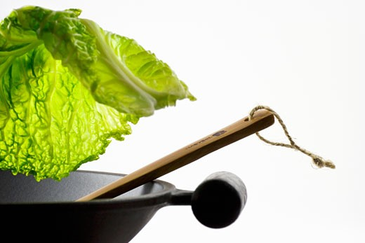 Savoy cabbage leaf falling into a wok : Stock Photo