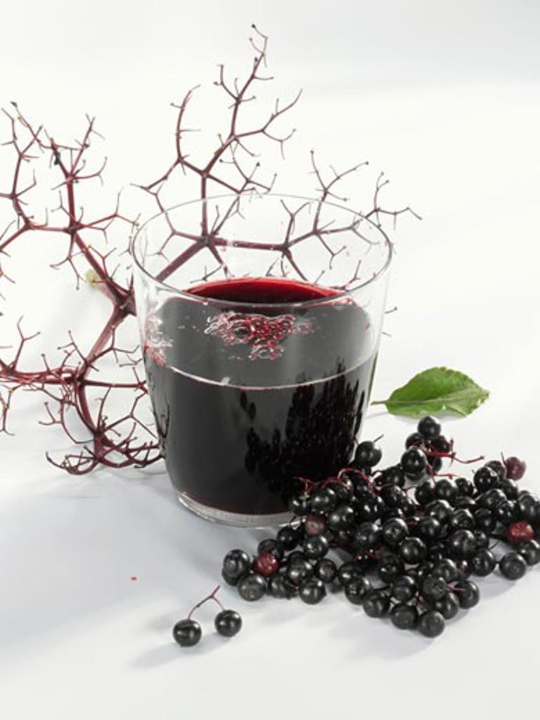 A glass of elderberry & apple juice & fresh elderberries : Stock Photo