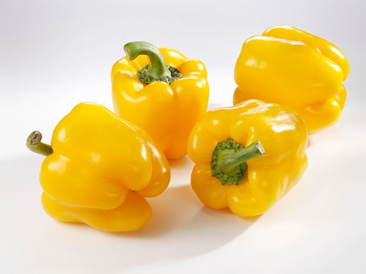 Four yellow peppers : Stock Photo