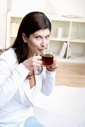 Woman drinking a cup of tea : Stock Photo