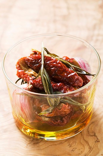 Dried tomatoes with rosemary, garlic and olive oil : Stock Photo