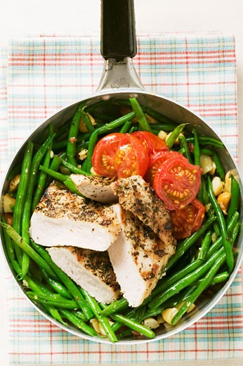 Chicken breast with green beans and tomatoes in frying pan : Stock Photo