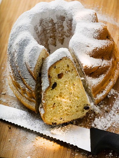 Gugelhupf with icing sugar, partly sliced : Stock Photo