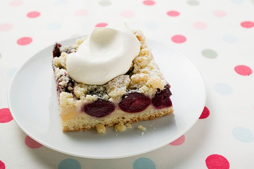 A piece of cherry crumble cake with cream : Stock Photo