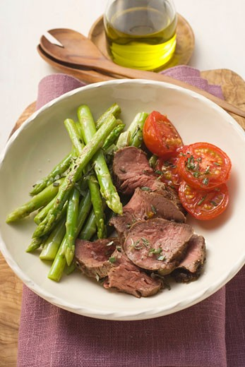 Beef with green asparagus and tomatoes : Stock Photo