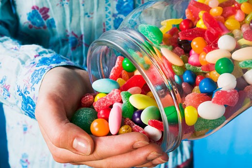 Stock Photo: 1532R-26804 Person tipping sweets out of jar