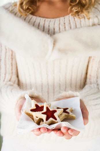 Stock Photo: 1532R-27128 Girl holding jam biscuits on napkin
