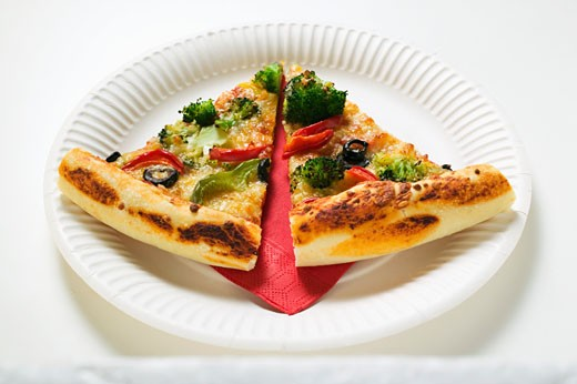 Two slices of American-style vegetable pizza on paper plate : Stock Photo