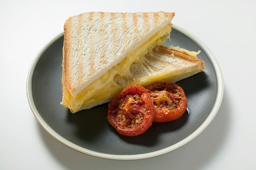 Toasted cheese sandwiches and grilled tomatoes on plate : Stock Photo