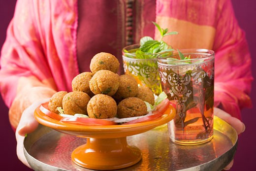 Stock Photo: 1532R-28338 Woman holding tray of falafel (chick-pea balls) and tea