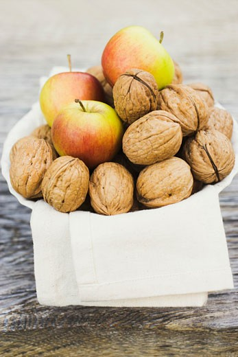 Walnuts and apples on cloth in white bowl : Stock Photo
